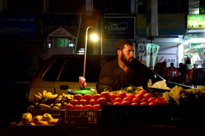 ISLAMABAD: November 08 – A vendor waiting for customers at his roadside fruit setup in the federal capital. APP photo by Irshad Sheikh