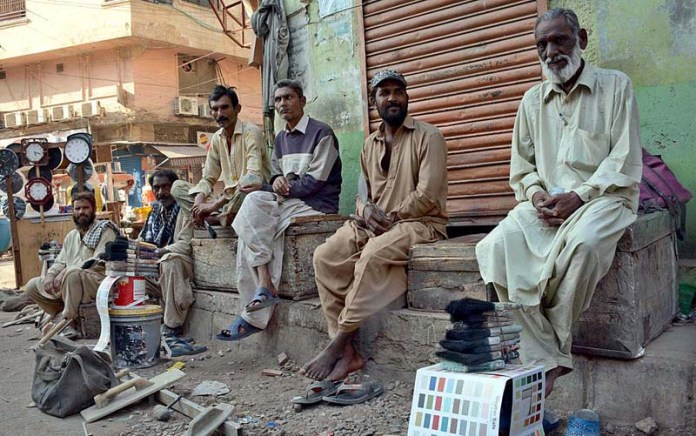 Daily wagers along with their tools sitting at a roadside waiting for customers