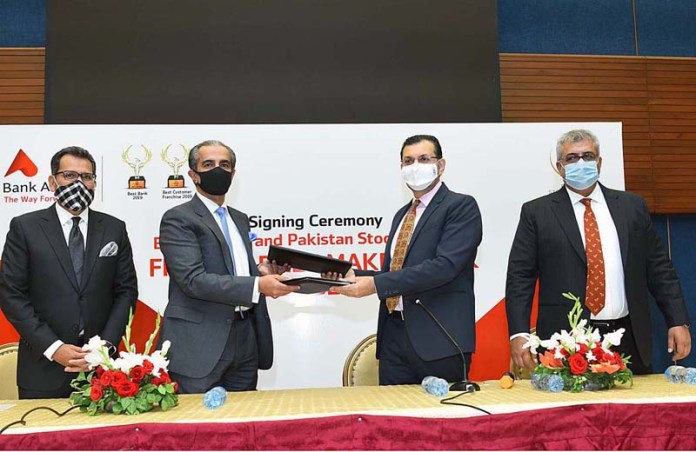 Chief Executive Officer Pakistan Stock Exchange Farrukh H Khan and President and CEO Bank Al-Falah Atif Bajwa exchanging documents after signing the agreement at Pakistan Stock Exchange