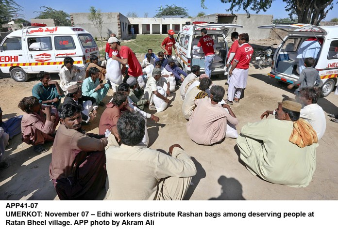 UMERKOT: November 07 – Edhi workers distribute Rashan bags among deserving people at Ratan Bheel village. APP photo by Akram Ali
