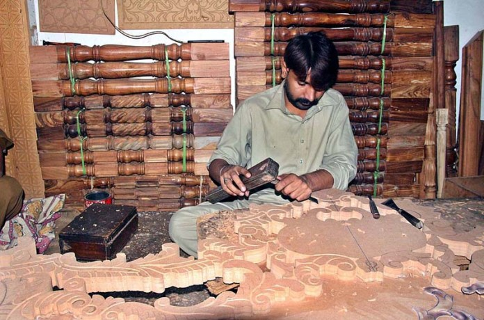 LAHORE: November 03 - A worker carving different designs on wooden piece at his workplace. APP photo by Tabasam Naveed