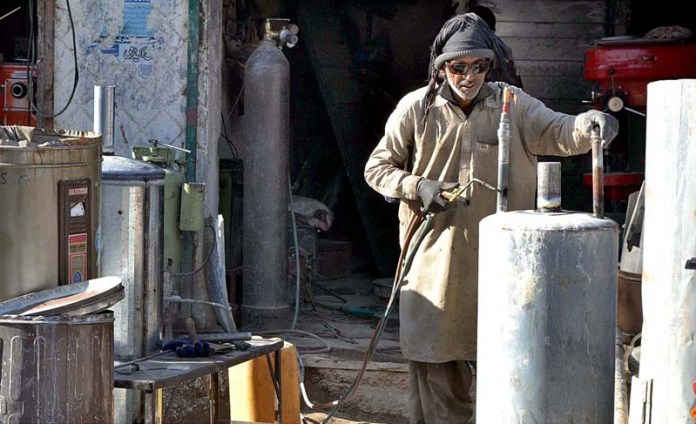 Geysers being repaired by a shopkeeper outside his shop at Makangi Road