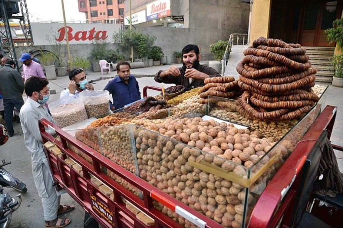 LAHORE: November 08 – A vendor displaying and selling dry fruits at his roadside setup. APP photo by Amir Khan