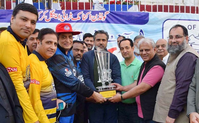 SIALKOT: November 08 – President Chamber of commerce Qaiser Iqbal Baryar giving away winner trophies to Fazal Jilani during Golden Economic Triangle Cricket Festival at Jinnah stadium. APP photo by Muhammad Munir Butt