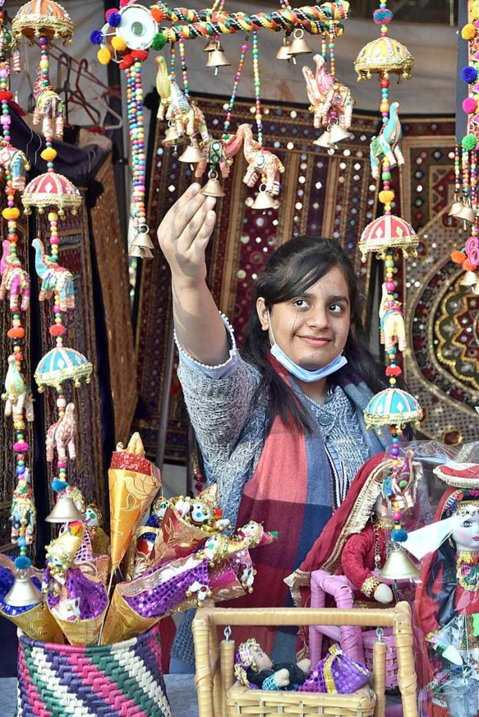"ISLAMABAD: November 07 – A visitor selects a miniature work at a stall during Folk Festival of Pakistan ""LOK MELA"" at Lok Virsa Shakarparian. APP photo by Irfan Mahmood"