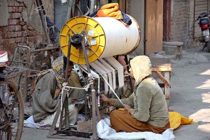 Workers busy in their routine work in a power loom factory