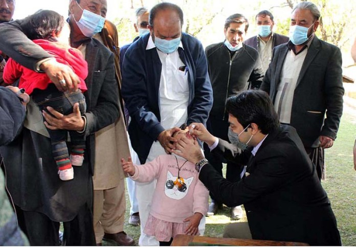 Health worker administering polio drop to children during 5-day of anti-polio campaign in the city