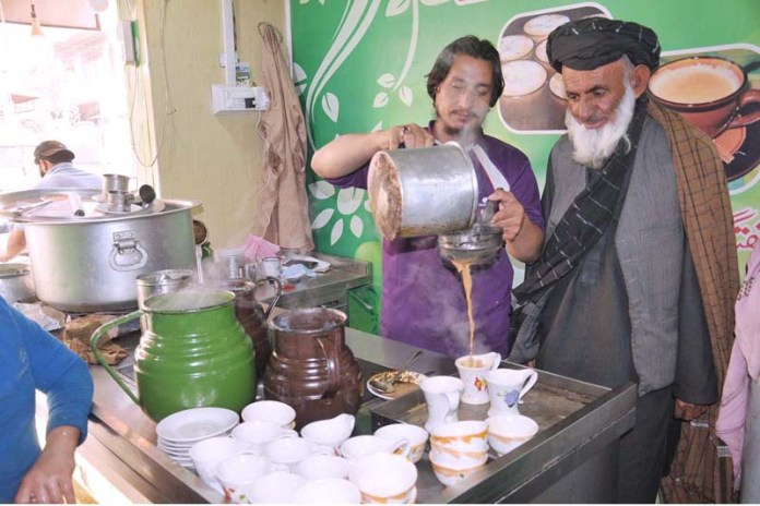 A vendor preparing tea for customers in a traditional way at his setup