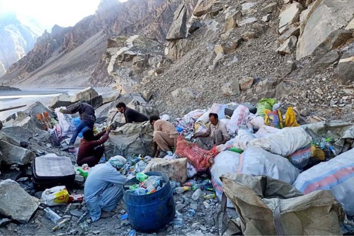 A group of needy persons searching for useful items from the road side garbage for domestic use