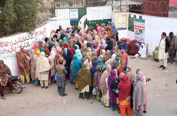 - Ladies standing in collecting financial aid under PM Ehsaas programs at Government Girls Higher Secondary Schoo