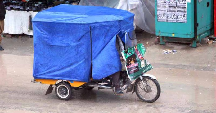 - A fully covered rickshaw on the way transporting passengers during rain that experienced in twin cities