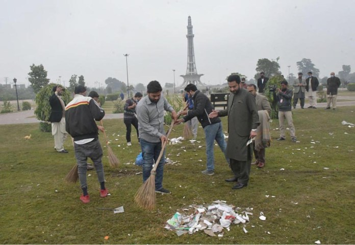 PTI workers busy in cleaning the ground after PDM public meeting at Minar-e-Pakistan