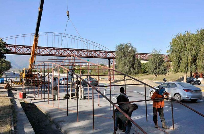 Labourers busy in installing pedestrian bridge at Expressway G-7 in Federal Capital