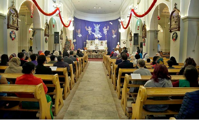 A Roman Catholic Archbishop Joseph Arshad reading Holy Bible prior to giving a sermon during the Christmas Service at St. Joseph's Catholic Cathedral at Lalkurti