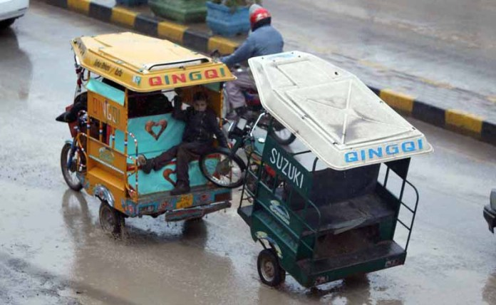 A rickshaw driver on the way toeing an out of order rickshaw during rain that experienced in twin cities