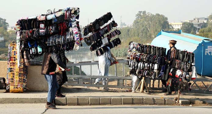 Vendors displaying different kinds of stuff to attract customers at their roadside setups at Moti Mahal