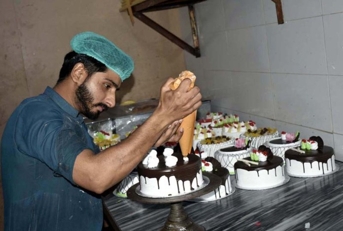 A worker busy in decorating cake in a bakery