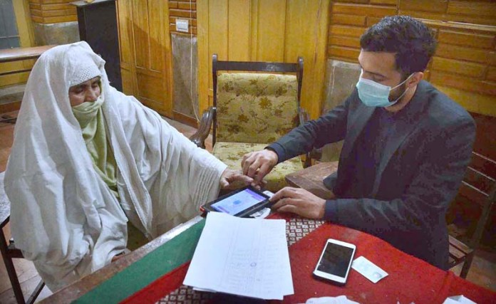 BISP officer verifying through NIC and biometric of deserving people during receiving relief fund Benazir Income Support Program from Government Shaheed Mubeen Shah Afridi Higher Secondary Cantt No 1 School