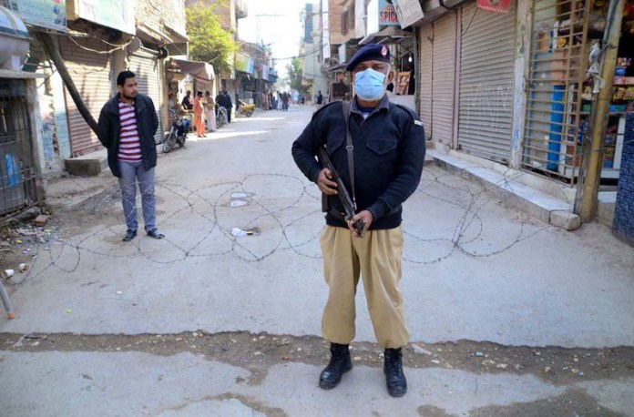 Police official stand in front of barbed wires at Mir Fazal Town during smart lockdown after COVID-19 cases in area at Taluka Latifabad