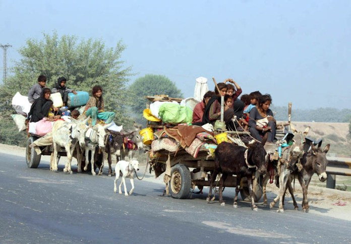 Gypsy family traveling on the donkey cart along with their household items heading towards their new destination