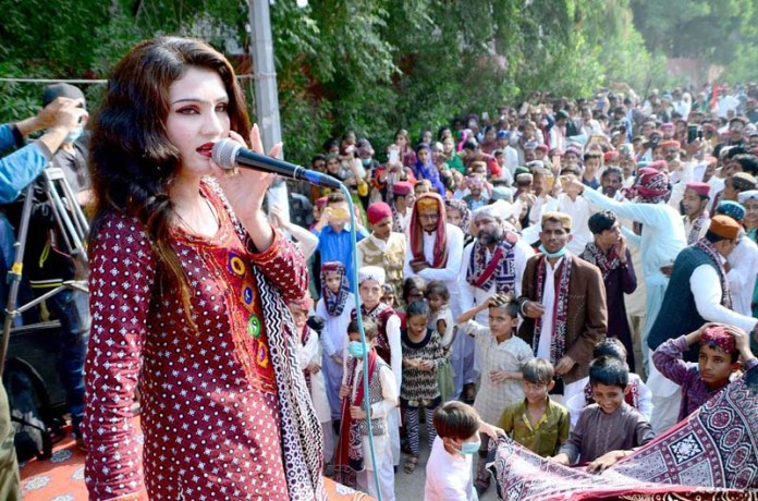 A folk singer performs on the stage during Sindhi Musical Program in connection with Sindhi Culture Day outside press club