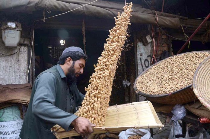 A laborer cleaning peanuts in a traditional way in Firdous Market