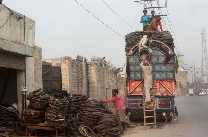 Labourers busy in loading old tyres on the delivery truck at Canal Road