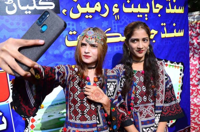 Girls taking selfie with wearing the Sindhi culture dresses during Sindhi Culture Day