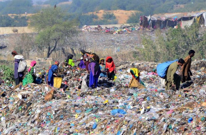 Gypsy persons searching valuables items from garbage at Latifabad