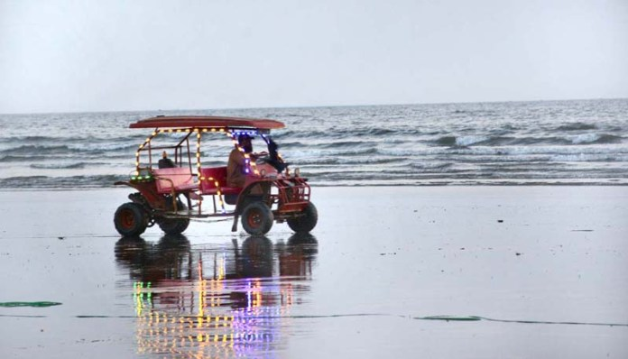 A man enjoying by driving lighting installed lights car at sea shore in Provincial Capital