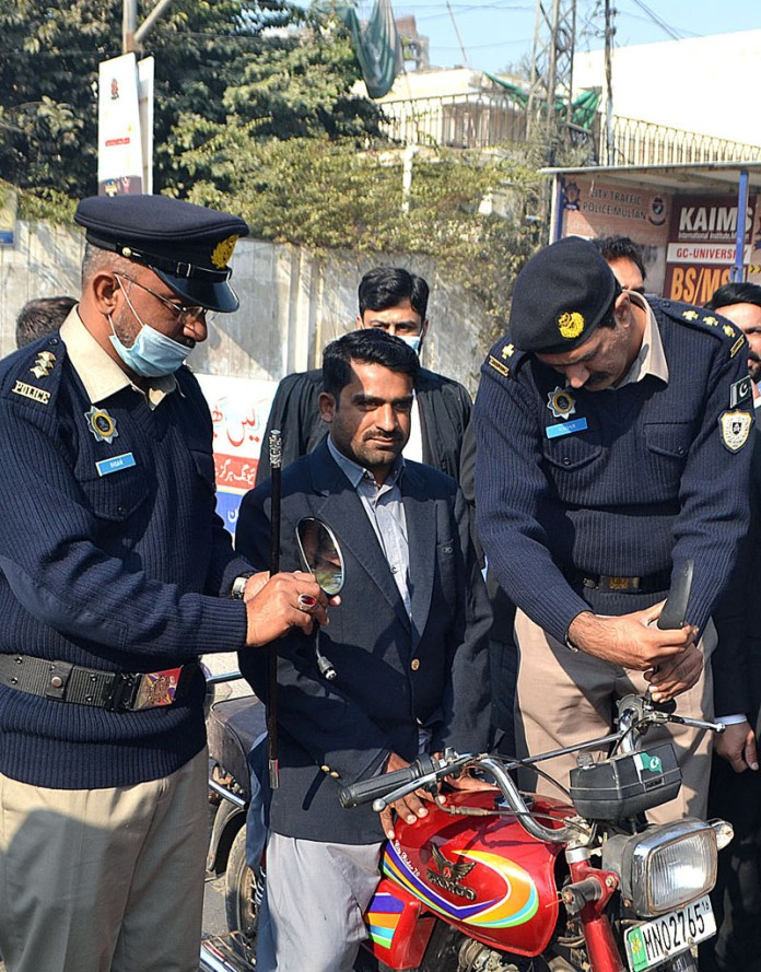 Police official fixing mirrors on a motorcycle during three days traffic awareness on fog organized by City Traffic Police at SP Chowk