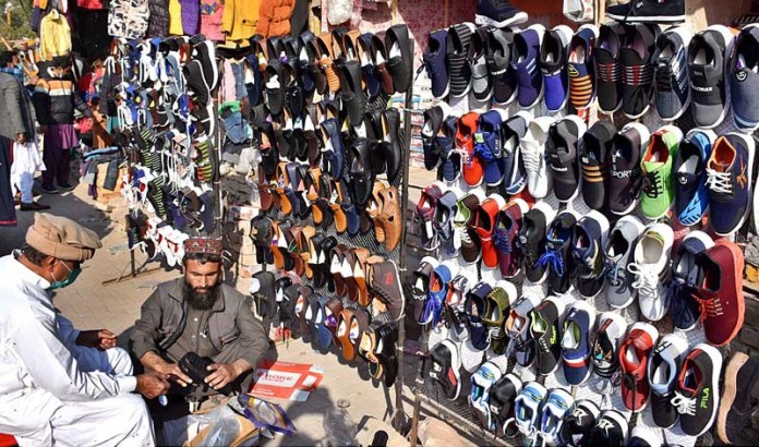 A vendor displaying and arranging shoes to attract customers at his roadside setup