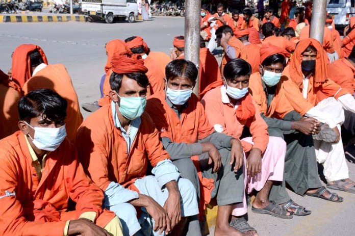 Porters (Coolies) wearing face masks to protect from COVID-19 sits at Cantt Station Sindh Government takes strict measures for the prevention of spread of COVID-19 pandemic in Provincial Capital