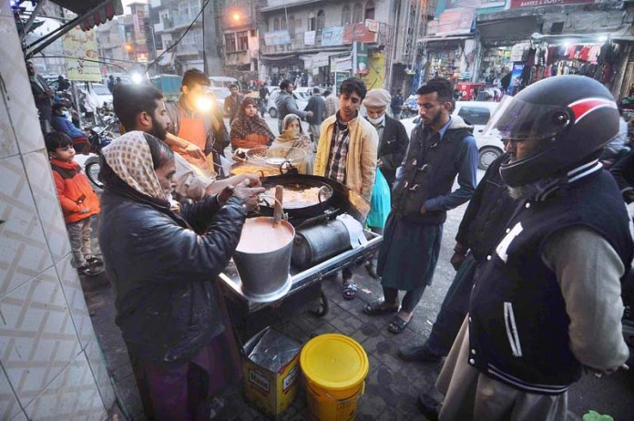 A large number of people purchasing traditional sweet food item Jalebi from a roadside vendor in a local market
