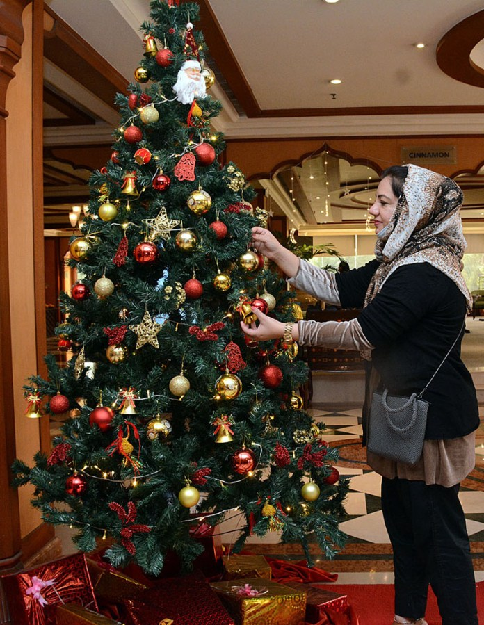 A female keenly viewing the Christmas tree installed in connection for upcoming celebrations of Christmas at a local hotel