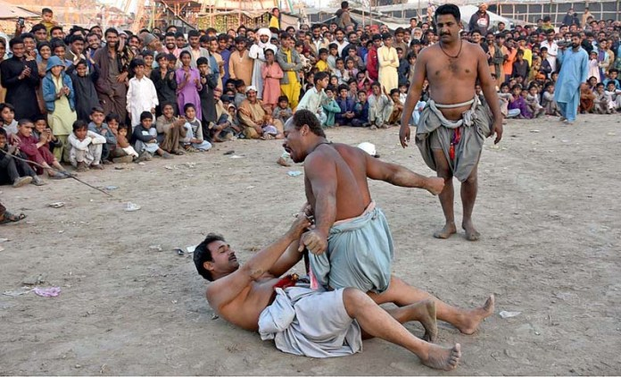 Wrestlers in action during traditional wrestling (Mulakhara) in front of Syed Ismail Shah Bukhari Shrine during annual urs celebrations near Rasheed Wagan Road
