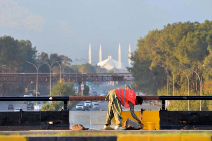 Labourer busy in paints protective wall on bridge in Federal Capital