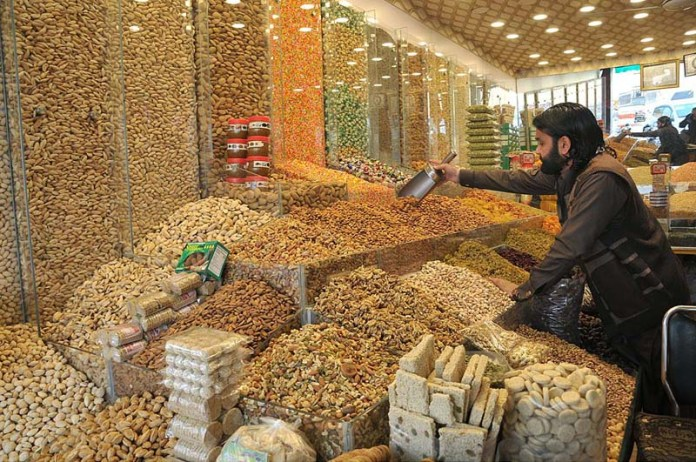 A vendor selling dry fruits at his shop in a local market of Federal Capital
