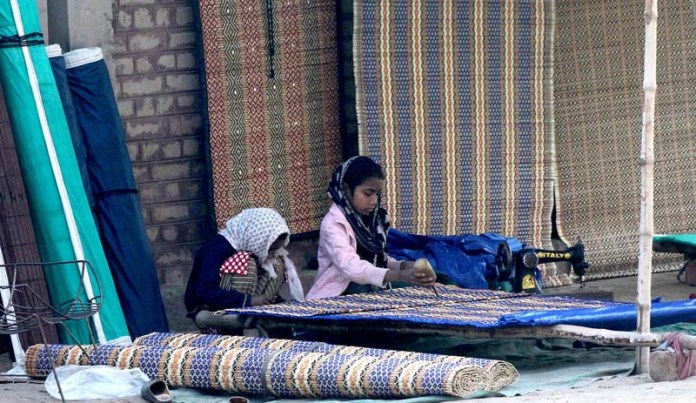 Child workers busy in making traditional curtain (Chik) near Dera Adda