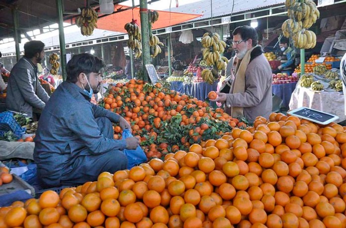 A vendor displaying oranges to attract the customers at weekly bazaar