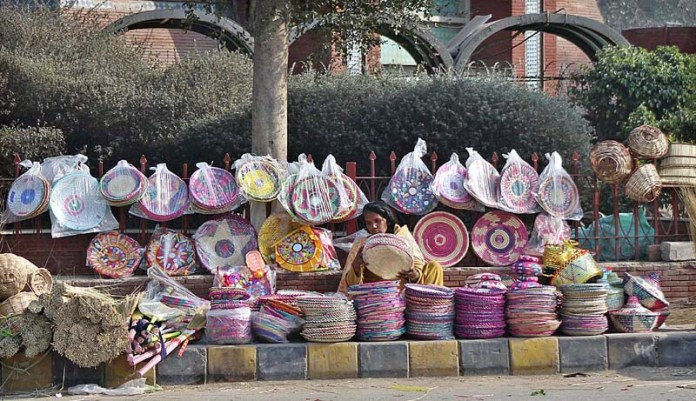 A female vendor busy in arranging and displaying household items to attract the customers at her roadside setup