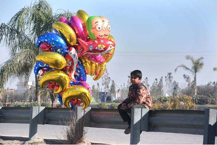 A youngster waiting for customers to sell different cartoon shape balloons at Northern Bypass