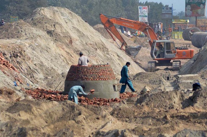 Labourers busy in construction work of main sewerage line near Northern Bypass during development in the city