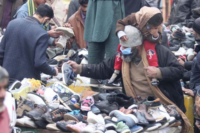 A man carrying his daughter on his shoulder selecting shoes from a road side vender's setup at landa bazar