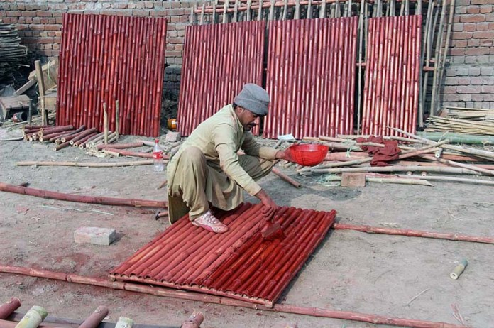 A worker busy in preparing bamboos fence at his workplace