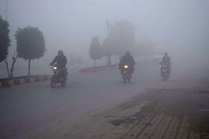 Motorcyclists on the way during thick fog that engulf the whole city during morning time