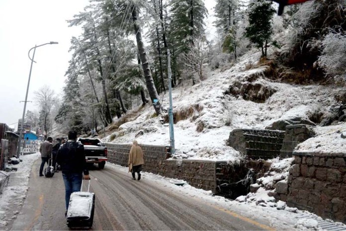 Tourist on their way during snow fall at the hilly town of Murree