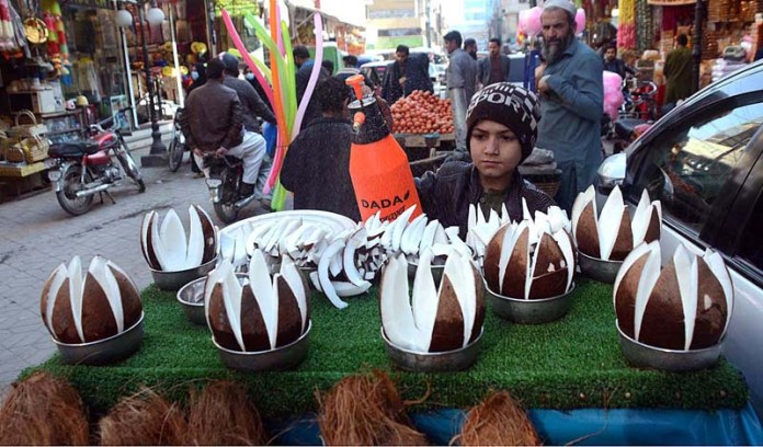 A young vendor displaying fresh coconut pieces to attract the customer near Fawara Chowk