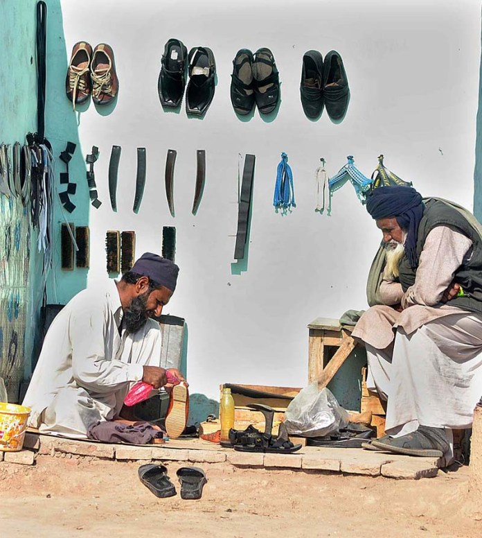 A cobbler busy in repairing shoes at his roadside setup