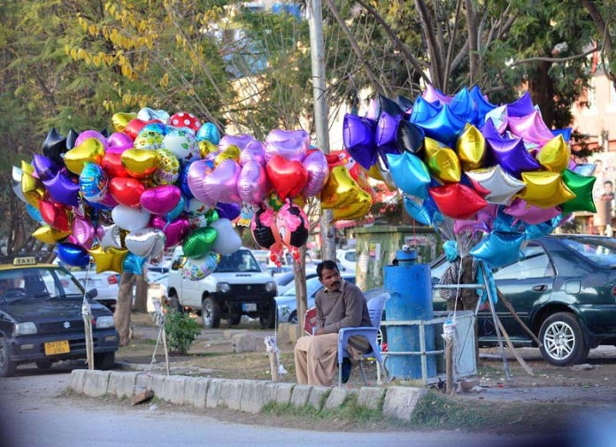 A vendor waiting for customers displaying colorful plastic toys along the roadside to earn livelihood